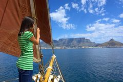 Shy girl on yacht with red sails looks at waves Stock Photography