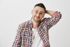 Shy guy tries to ask lovely woman for date. Portrait of happy charming young male with bristle in trendy eyewear holding. Hand on back of head and smiling royalty free stock photography