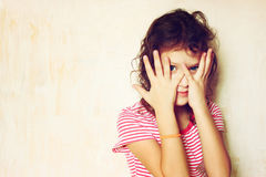 Shy kid peeking through civered face. filtered image Stock Images