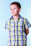 Shy little boy with hands behind back. Royalty Free Stock Image