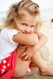 Shy little girl. Sitting and looking to the camera Stock Photos