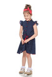 Shy little girl in the blue dress. stock photos