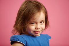 Shy little girl with cute look, close-up portrait on pink isolated background. stock photo