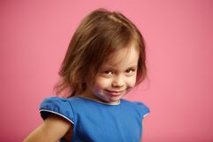 Shy little girl with cute look, portrait on pink isolated background. royalty free stock photos