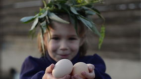 Shy little girl with fresh chicken eggs stock video