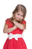 Shy little girl in the red dress. A portrait of a shy little girl in the red dress on the white background stock image