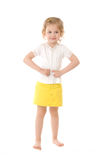 Shy little girl standing on white background. Shy little girl wearing a yellow skirt standing on white background Royalty Free Stock Image