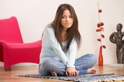 Shy look. Young lady with long dark brown hair, blue top and jeans, sitting on the floor of her living room Royalty Free Stock Photo