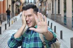 Shy man covering his face while smiling royalty free stock photography