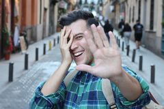 Shy man covering his face while smiling royalty free stock images