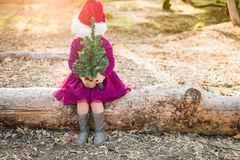 Shy Mixed Race Young Baby Girl Having Fun With Santa Hat and Christmas Tree. Cute Mixed Race Young Baby Girl Having Fun With Santa Hat and Christmas Tree royalty free stock images