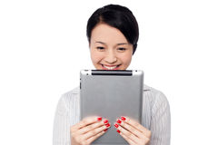 Shy pretty corporate lady holding tablet device Stock Images