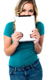 Shy pretty model hiding face with tablet pc Royalty Free Stock Image