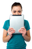Shy pretty model hiding face with tablet pc Stock Image
