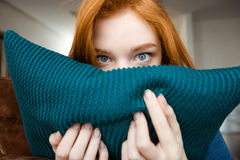 Shy pretty young woman  hiding face behind knitted pillow Royalty Free Stock Photography