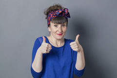 Shy retro 30s woman smiling with two thumbs up Stock Photography