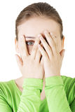 Shy or scared teenage girl peeking through covered face. Isolated on white Royalty Free Stock Photography