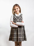 Shy schoolgirl in checkered dress against white background Royalty Free Stock Photography