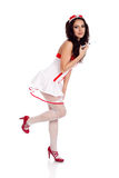 Shy sexy nurse holding a leg up. Full body shot of a sexy beautiful young nurse wearing red high heels shoes holding a syringe on isolated white background. High Stock Images