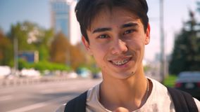 Shy sincere smile of asian man in braces looking straight at camera, showing braces while standing on the road