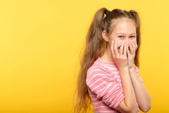 Shy smiling embarrassed girl covering mouth hands. Shy smiling embarrassed girl covering mouth with hands. young cute child emotional portrait on yellow stock photography