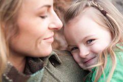 Shy smiling little girl with mother stock photography