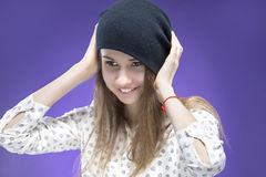 Shy and Smiling Young Caucasian Girl Holding Black Hat Posing Against Violet Background Royalty Free Stock Photography