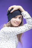 Shy and Smiling Young Caucasian Girl Holding Black Hat Posing Against Violet Background Royalty Free Stock Photos