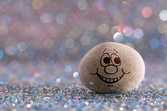 The shy stone emoji. Emotions on color glitter boke background stock photography