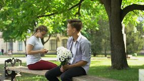 Shy teen with flowers sitting next to lady, surfing net on phone, hesitation. Stock footage stock video footage