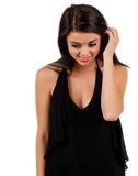 Shy teen girl. An embarassed shy teen girl runs her fingers through her hair as she looks down at the floor in front of her royalty free stock images