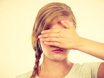 Shy teenage girl hiding face behind hand. Anxiety, bullying at school concept. Shy teenage girl covering her face with hands Royalty Free Stock Photography