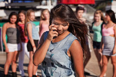 Shy Teenage Girl Looking Down. Shy teenage Filipino girl looking down with friends nearby Royalty Free Stock Photos