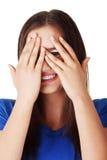 Shy teenage girl peeking through covered face. Isolated on white Stock Photo