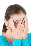 Shy teenage girl peeking through covered face Royalty Free Stock Photo