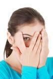 Shy teenage girl peeking through covered face. Isolated on white Royalty Free Stock Photo