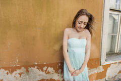 Shy teenage girl in tube dress standing against wall Stock Photo