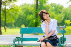 Shy Thai schoolgirl sitting on a bench closeup Royalty Free Stock Photos