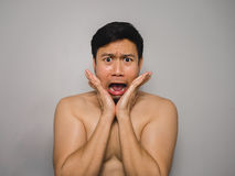 Shy topless man. Topless Asian man with funny act of shy and shocked Royalty Free Stock Image