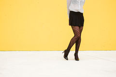 Shy trendy fashion businesswoman legs. Sexy businesswoman on shy legs pose wearing fishnet stockings and skirt. Trendy professional woman Royalty Free Stock Photos