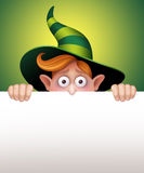 Shy wizard boy hiding, holding blank message card, Halloween banner illustration Royalty Free Stock Photo