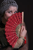 Shy woman with fan. Portrait of a shy or coy woman in vintage dress and hat, holding a red fan in front of her face.  Black background Royalty Free Stock Image