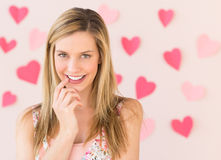 Shy Woman With Heart Shaped Papers Stuck Against Pink Background Royalty Free Stock Images