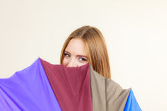 Shy woman hiding behind colorful umbrella Royalty Free Stock Photography