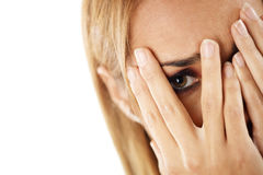 Shy woman looking through fingers Stock Image