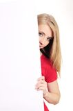 Shy woman looking over blank card Royalty Free Stock Photography