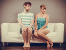 Shy woman and man sitting close to each other on couch. Stock Photos