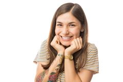 Shy Woman Smiling Over White Background. Young shy woman smiling over plain white background stock image