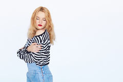 Shy young blond hair woman smiling with bare shoulder. Attractive beautiful girl with red lips posing on white background with copyspace royalty free stock photo