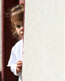 Shy young child hiding. Innocent shy girl hiding in door frame Royalty Free Stock Photo